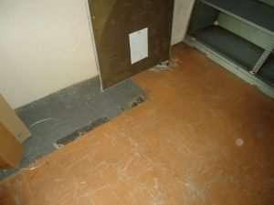 Asbestos vinyl tiles and bitumen adhesive